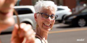 Older female with short white hair and dark glasses smiling